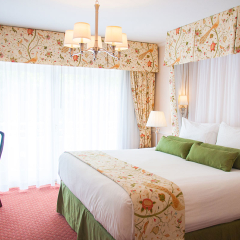 Deluxe King overview, white curtains and floral patterns
